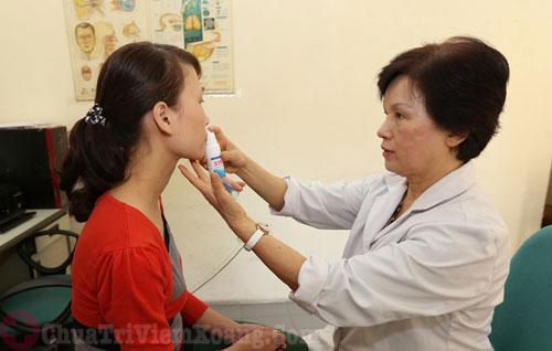 Hình ảnh bác sĩ hướng dẫn bệnh nhân dùng thuốc xịt mũi trị viêm mũi dị ứng